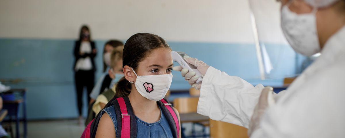 Pediatrician using thermometer temperature screening for school children