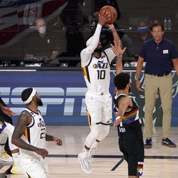 Utah Jazz's Mike Conley (10) attempts a shot in the final seconds of the second half of an NBA first round playoff basketball game as Royce O'Neale (23), Denver Nuggets' Gary Harris, left, Jamal Murray, bottom front and Jazz head coach Quin Snyder, right rear, look on, Tuesday, Sept. 1, 2020, in Lake Buena Vista, Fla.