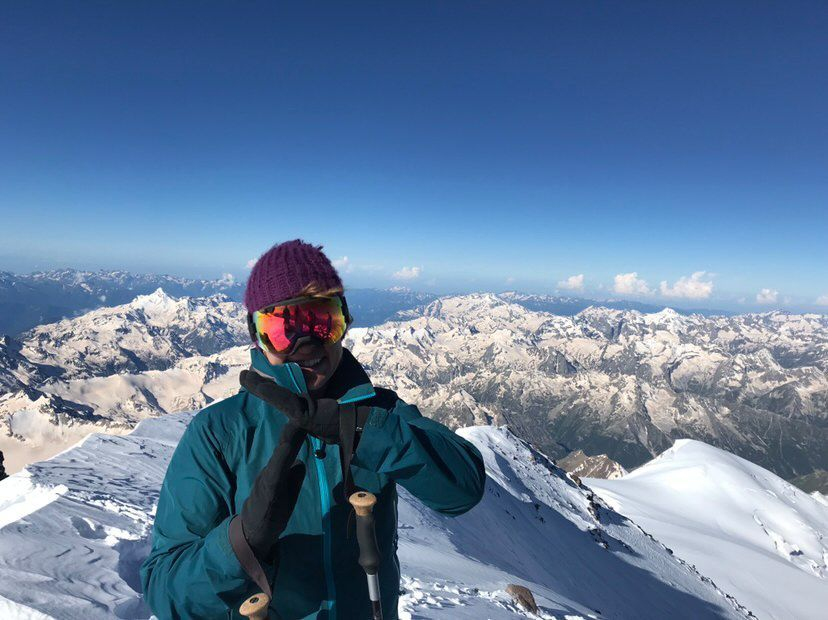 """Erin Parisi atop Mt Elbrus making a """"T"""" symbol with her gloved hands to show she is proudly trans"""