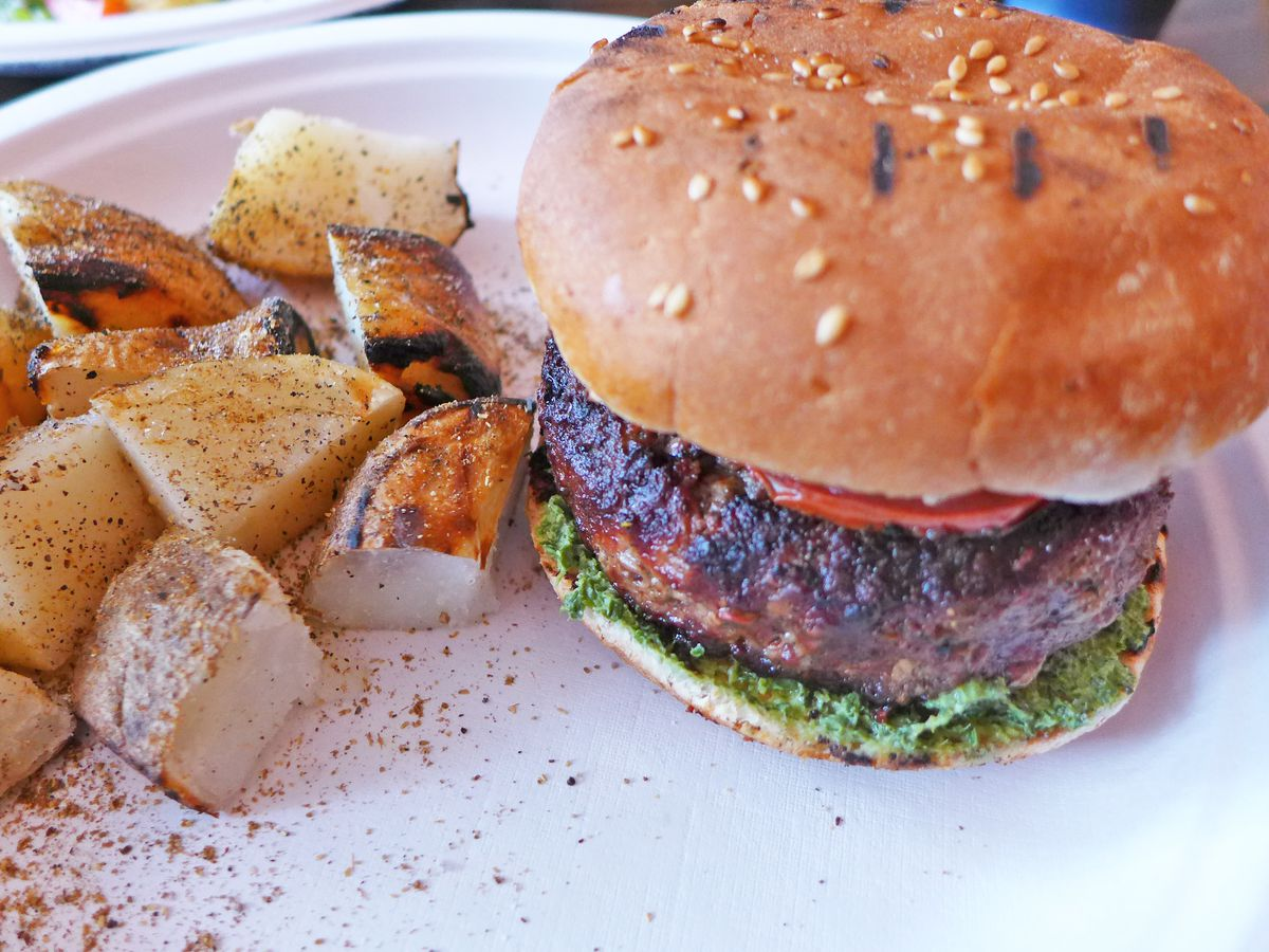 A blackened thick burger on a sesame seed bun with cubed potatoes on the side.
