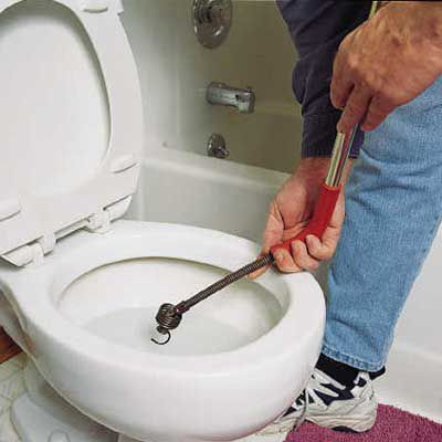 Person using a closet auger in a toilet bowl to clear a clog.