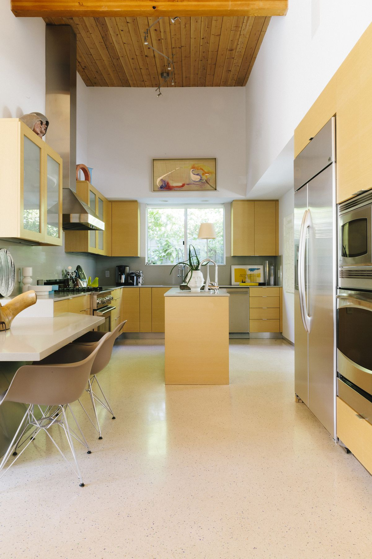 A kitchen with light yellow cabinetry. There is a wooden table with chairs. The ceiling is made of wood. There are windows over the sink area.