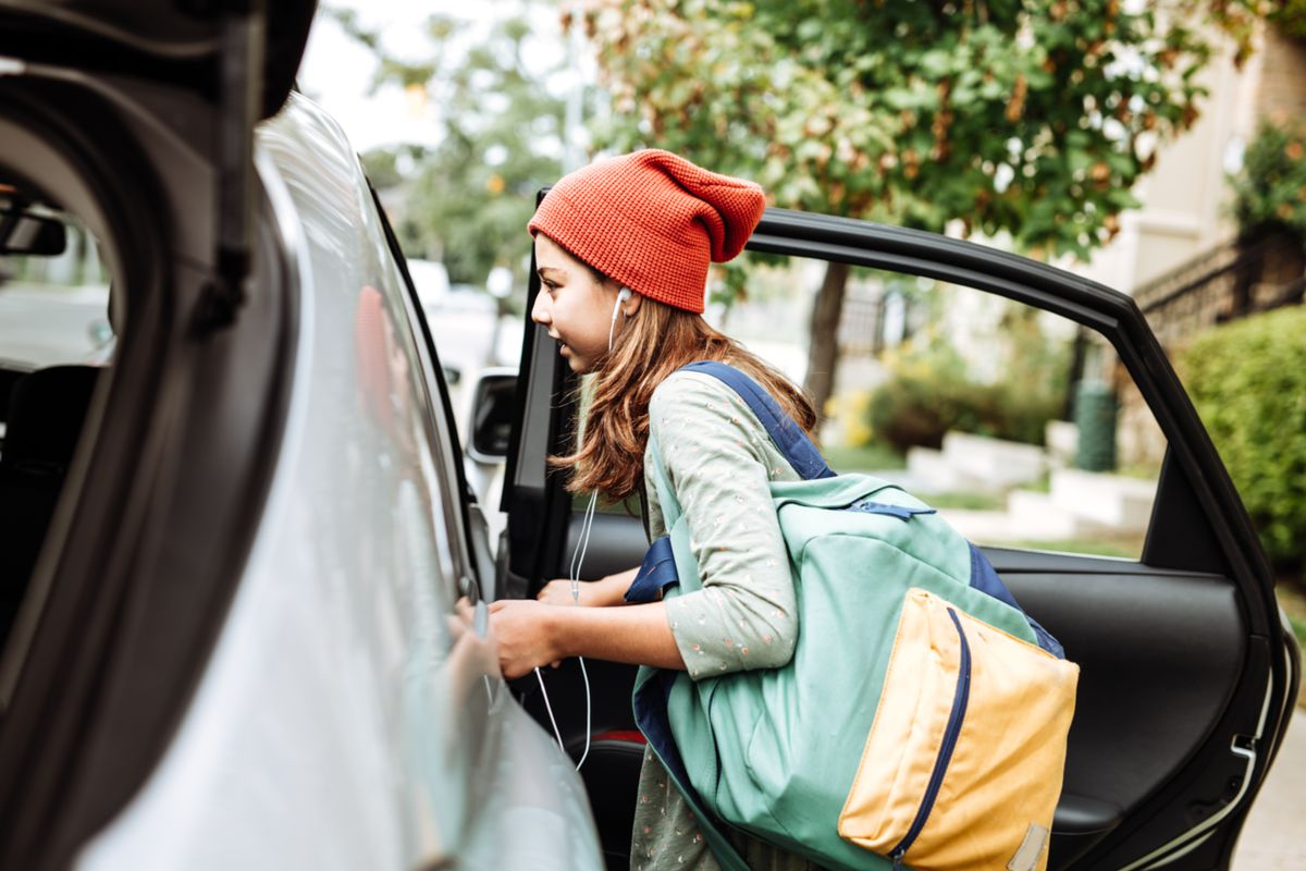 A teenager carrying a backpack getting into a car.