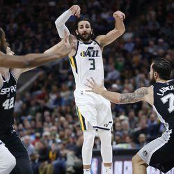 Utah Jazz guard Ricky Rubio (3) passes on San Antonio Spurs center Joffrey Lauvergne (77) in Salt Lake City on Thursday, Dec. 21, 2017.