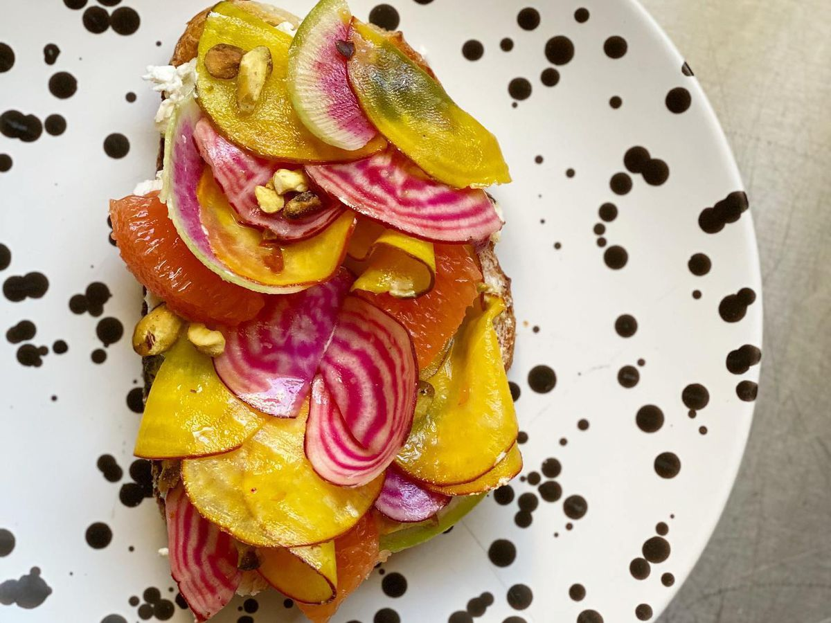 From above, a thick slice of bread layered with shaved beets and oranges, on a decorative polka dot plate