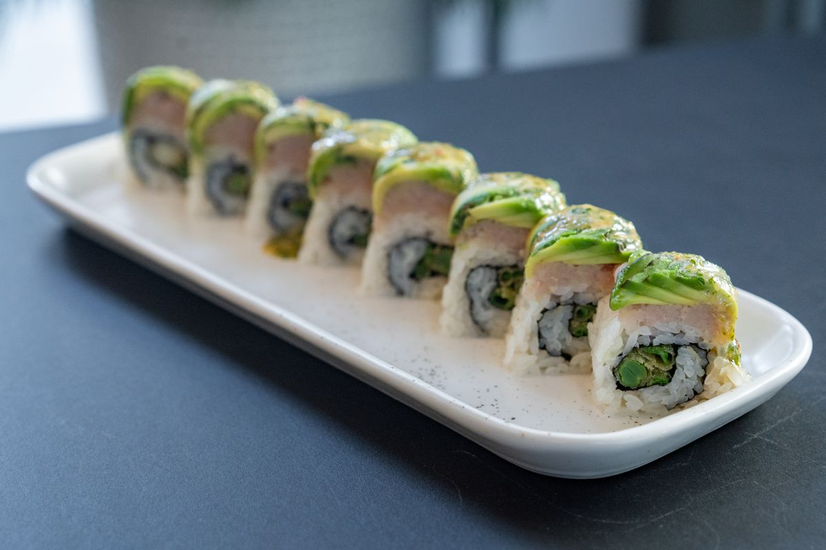 A sushi roll topped with green onion, avocado, cilantro sweet chile aioli, topped with albacore.