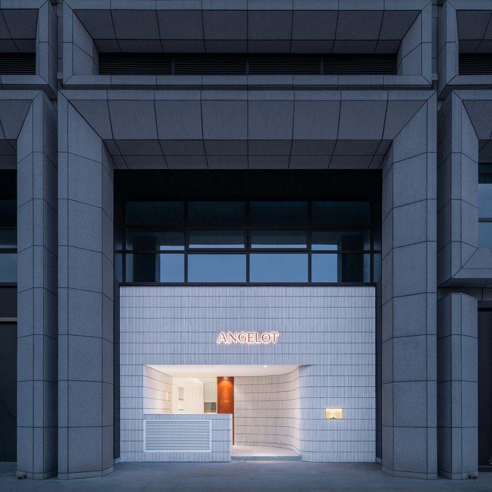 Glowing facade slotted into concrete facade.