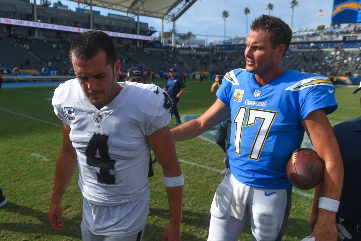 Oakland Raiders quarterback Derek Carr and Los Angeles Chargers quarterback Philip Rivers leave the field after the game at StubHub Center in Carson on Sunday, Oct. 7, 2018.
