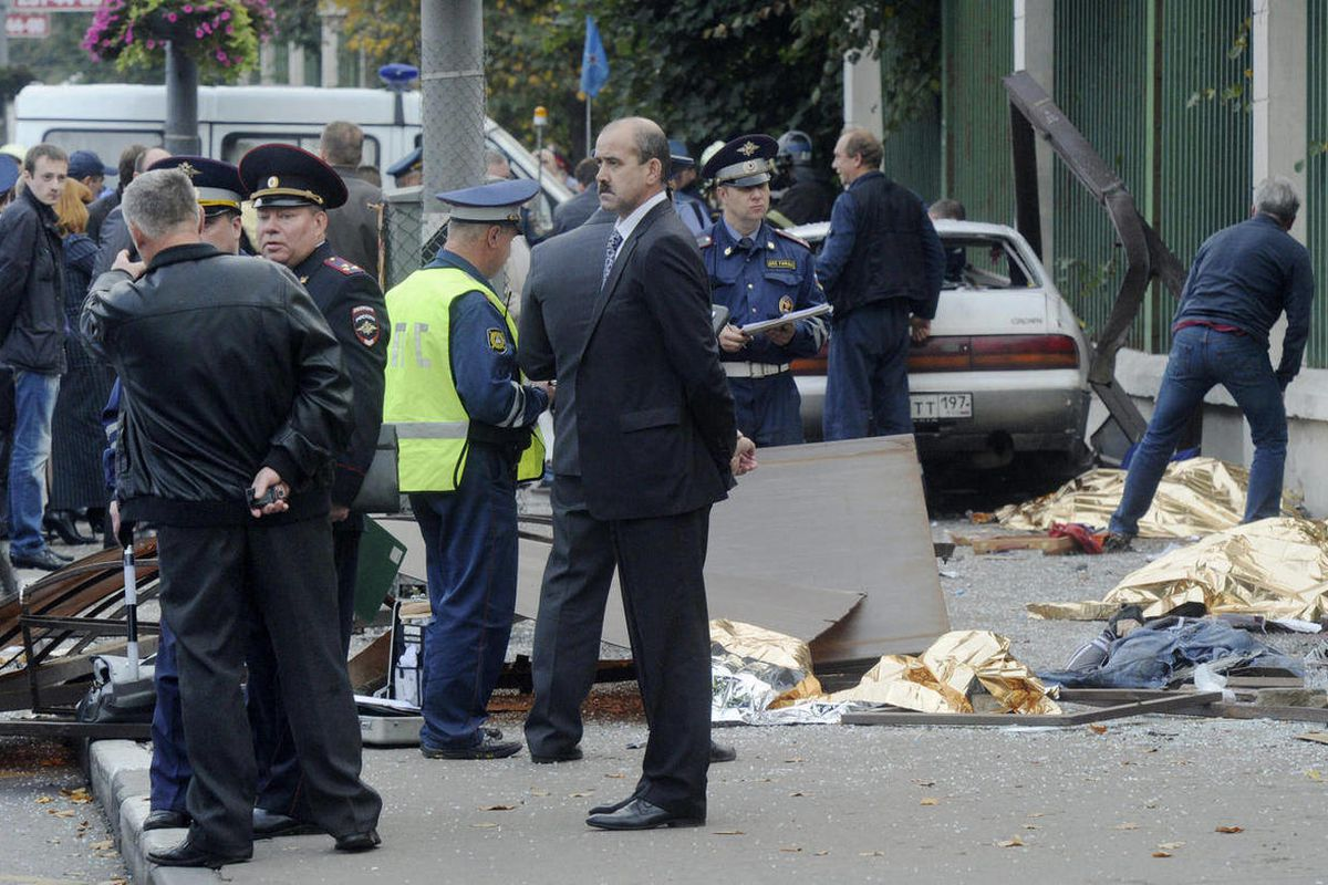 In this photo made Saturday, Sept. 22, 2012, law enforcement authorities work at the site of the crash where a heavily drunk driver killed seven people at a bus stop in Moscow, Russia.  Five orphaned teens were waiting for a bus with their guardians in Mo