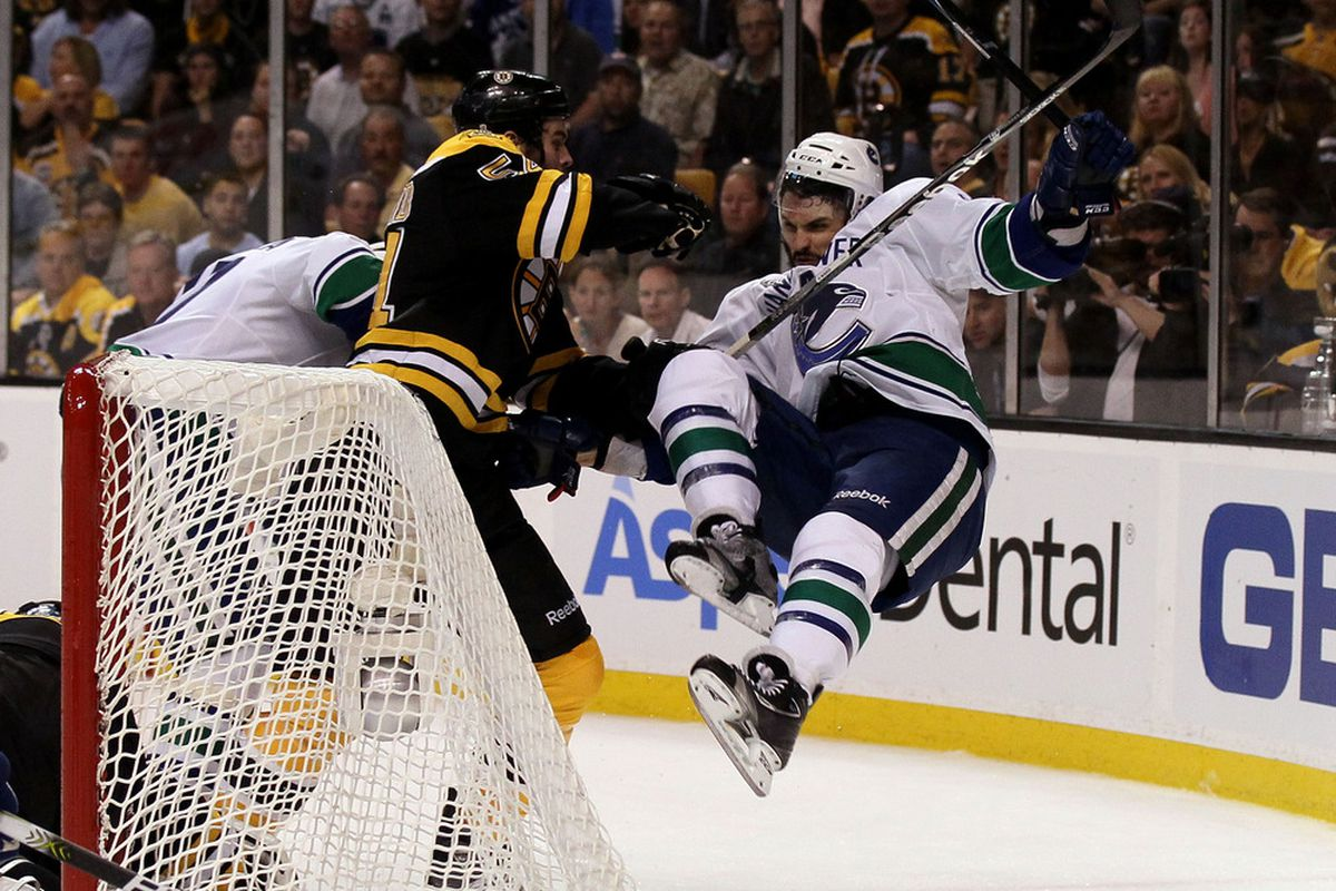 BOSTON, MA - JUNE 13:  Adam McQuaid #54 of the Boston Bruins checks Maxim Lapierre #40 of the Vancouver Canucks during Game Six of the 2011 NHL Stanley Cup Final at TD Garden on June 13, 2011 in Boston, Massachusetts.  (Photo by Elsa/Getty Images)