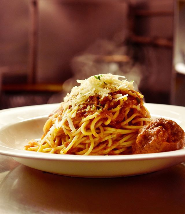A plate of spaghetti and meatballs, piled high, with steam coming up from it