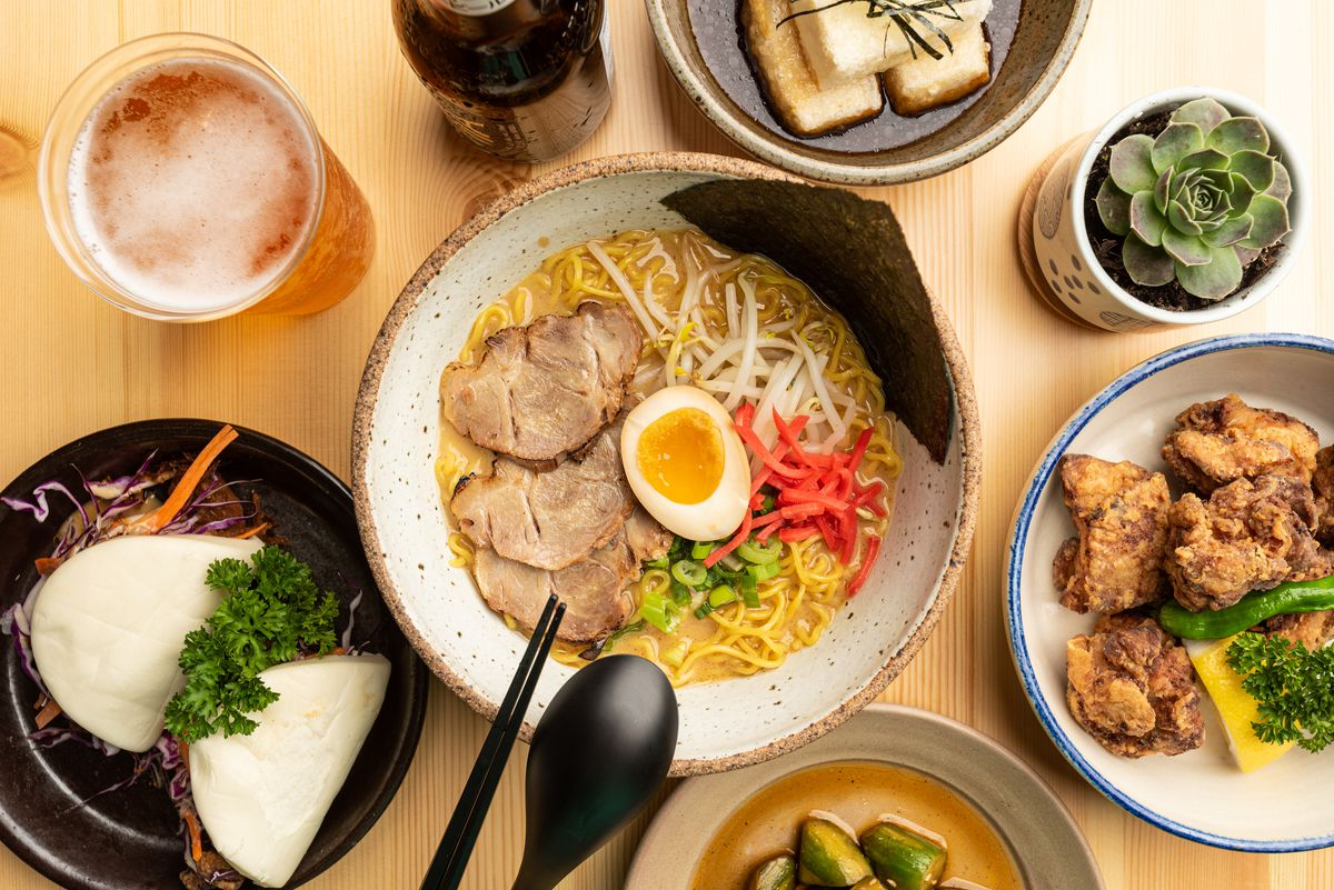 Array of dishes including buns, ramen noodles, fried chicken, and more on plates at Moto Ramen.