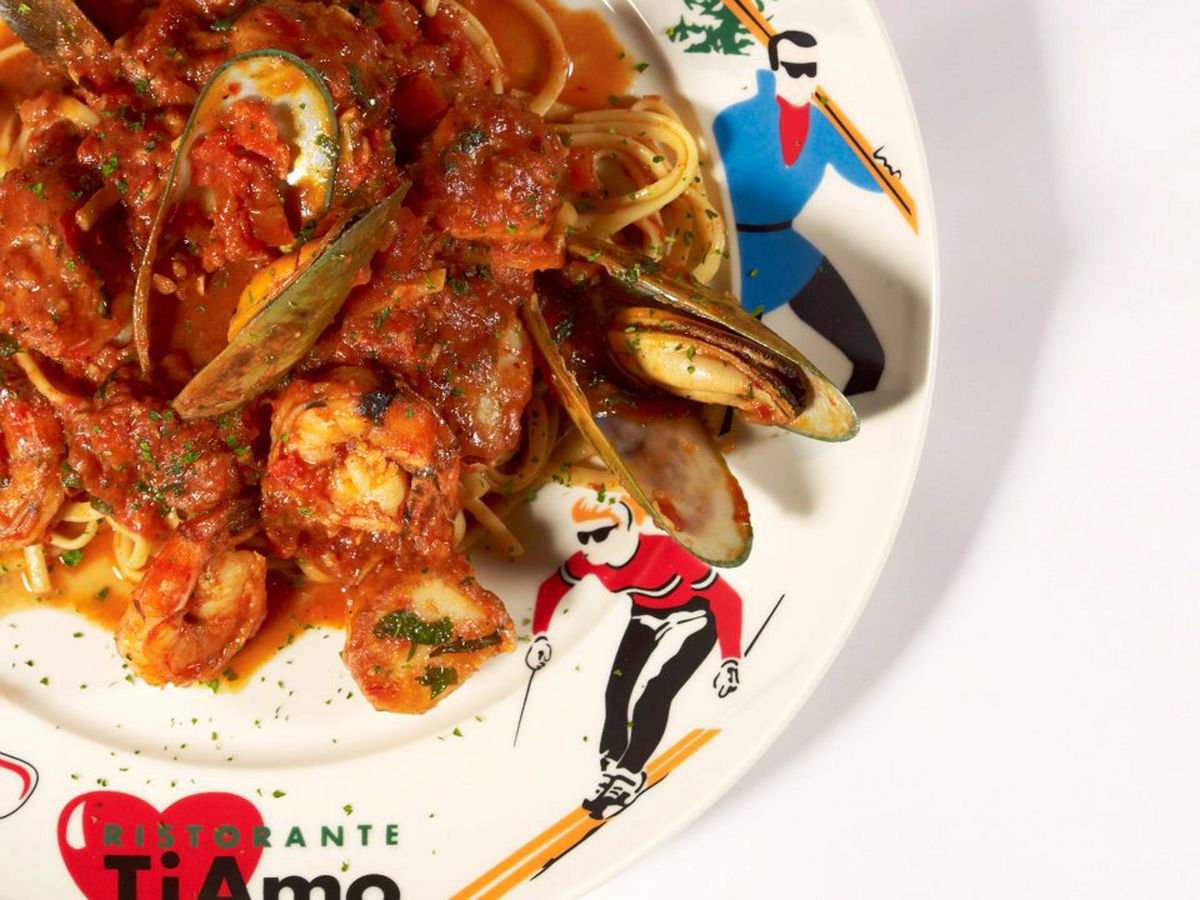 A plate illustrated with simple skier figures filled with mussels, shrimp, and scallops in sauce over linguine