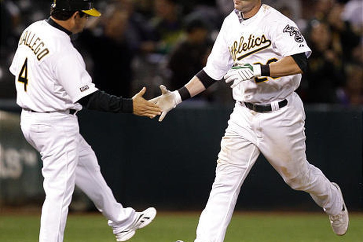 Oakland Athletics' Adam Kennedy, right, is congratulated by third base coach Mike Gallego after hitting a two-run home run off Texas Rangers' Neftali Feliz.
