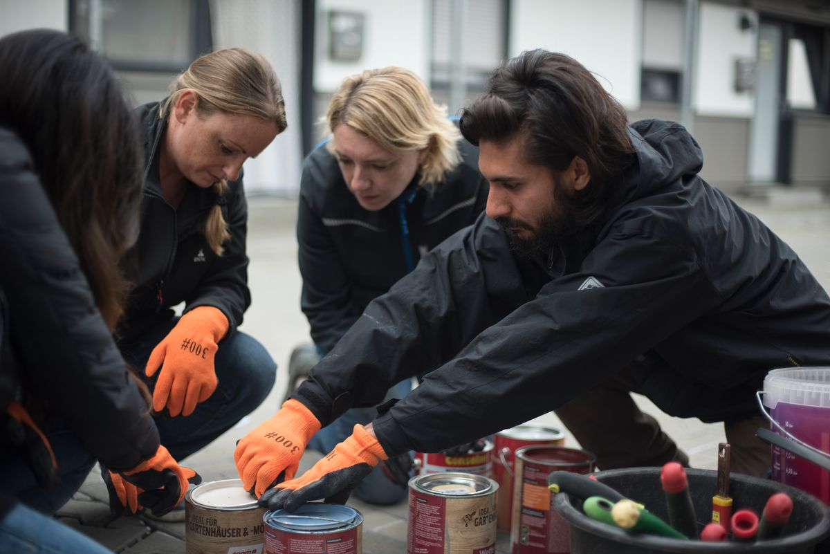 Refugee shelter social worker Hamza Tariq, 28, right, helps volunteers from the company CBRE to open some paint cans during a social service day the company was putting on at a refugee shelter in Nied, Germany, on Friday, Sept. 13, 2019. The team was painting several raised flower beds and some outdoor furniture for the facility.