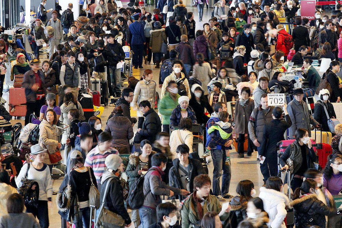 FILE - In this March 18, 2011 file photo, evacuees and regular passengers crowd a check-in area at Narita airport in Narita, east of Tokyo, following advisories from foreign governments recommending citizens leave the country as the crisis at Japan's Fuku
