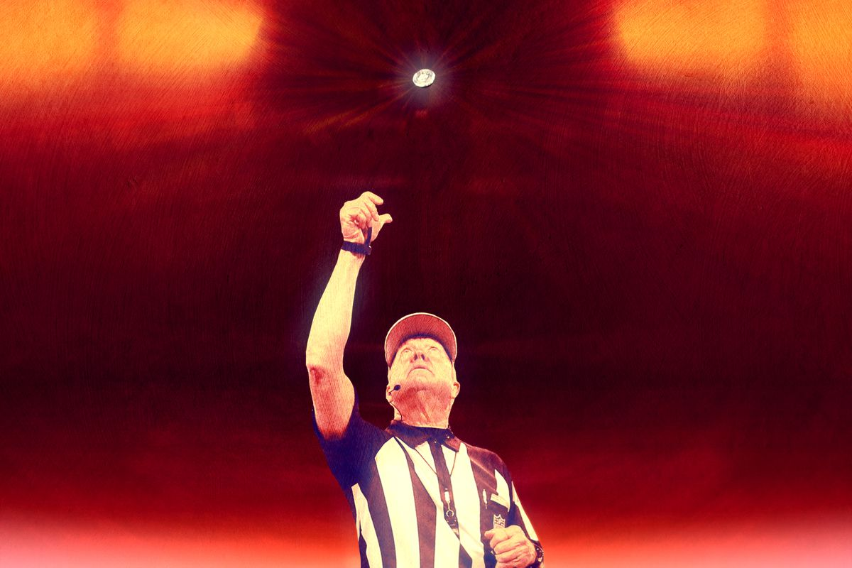 An NFL referee raising his right hand in the air