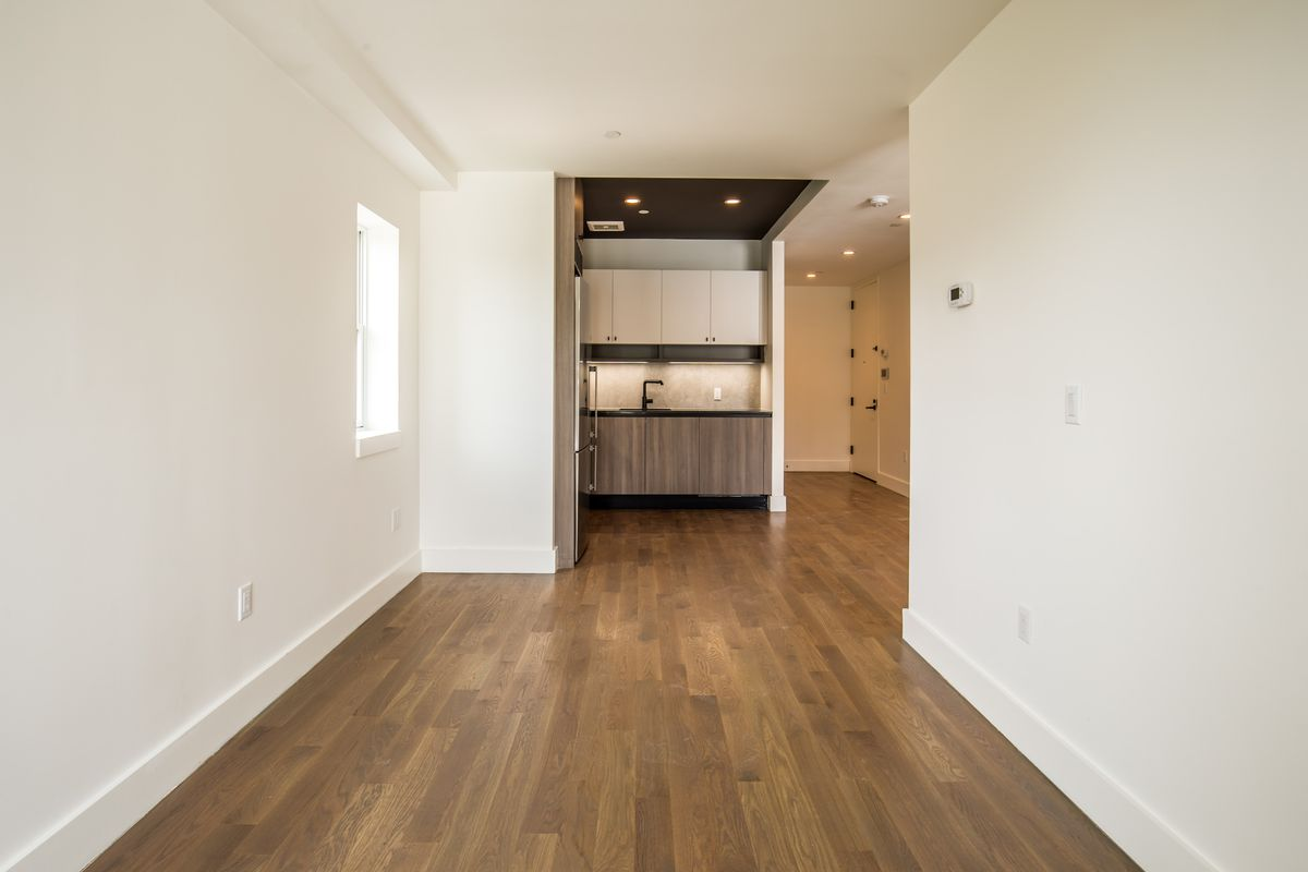 A living area with hardwood floors, beige walls, and a small open kitchen in the back.