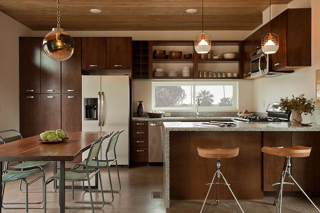 A kitchen area with counters, stools, a table, chairs, refrigerator, and wood cabinetry.