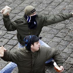 Protesters throw rocks at police during clashes in Zagreb, Croatia, Saturday, Feb. 26, 2011. Some 15,000 anti-government protesters rallied in the Croatian capital and some clashed with police.