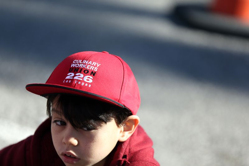 "Young boy wearing red hat that reads ""Culinary Workers Union 226 Las Vegas."""