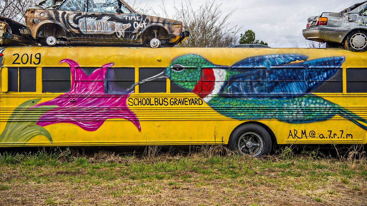 A hummingbird mural painted on a school bus with rusted old cars on the top.