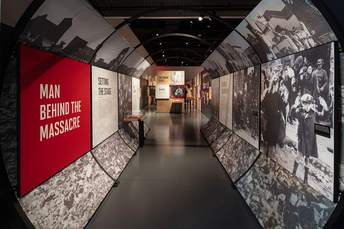 """An exhibition set in a tunnel-like hallway contains blown-up black-and-white images on either side of the hallway. The words """"MAN BEHIND THE MASSACRE,"""" lettered in white and placed on a red background, can be read on the left side of the picture."""