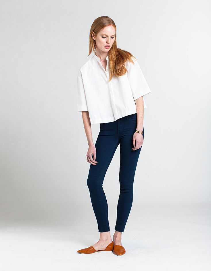 5e724a602e A model wearing dark denim mid rise jeans and a white shirt