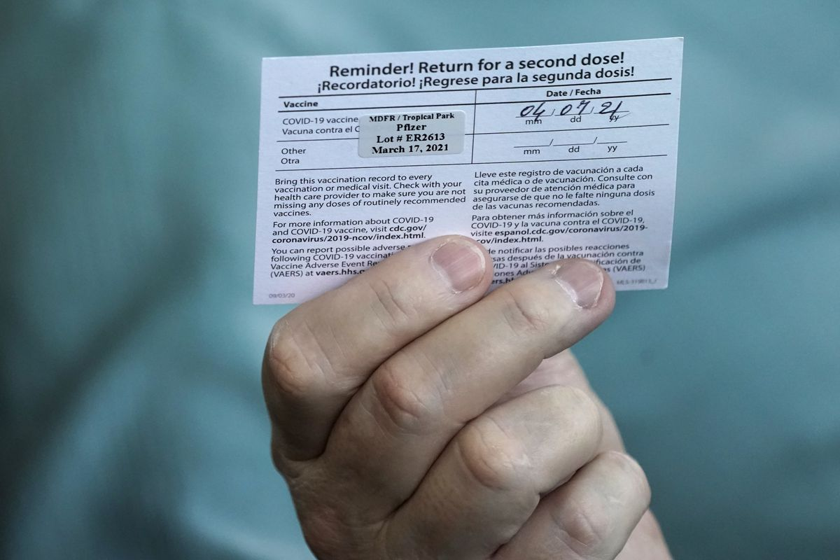 Juan Carlos Guerrero, 62, holds his second shot reminder card after receiving a dose of the Pfizer's COVID-19 vaccine.