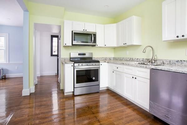 A renovated kitchen with an L-shaped counter and a new stove, and there are doors leading off the room.