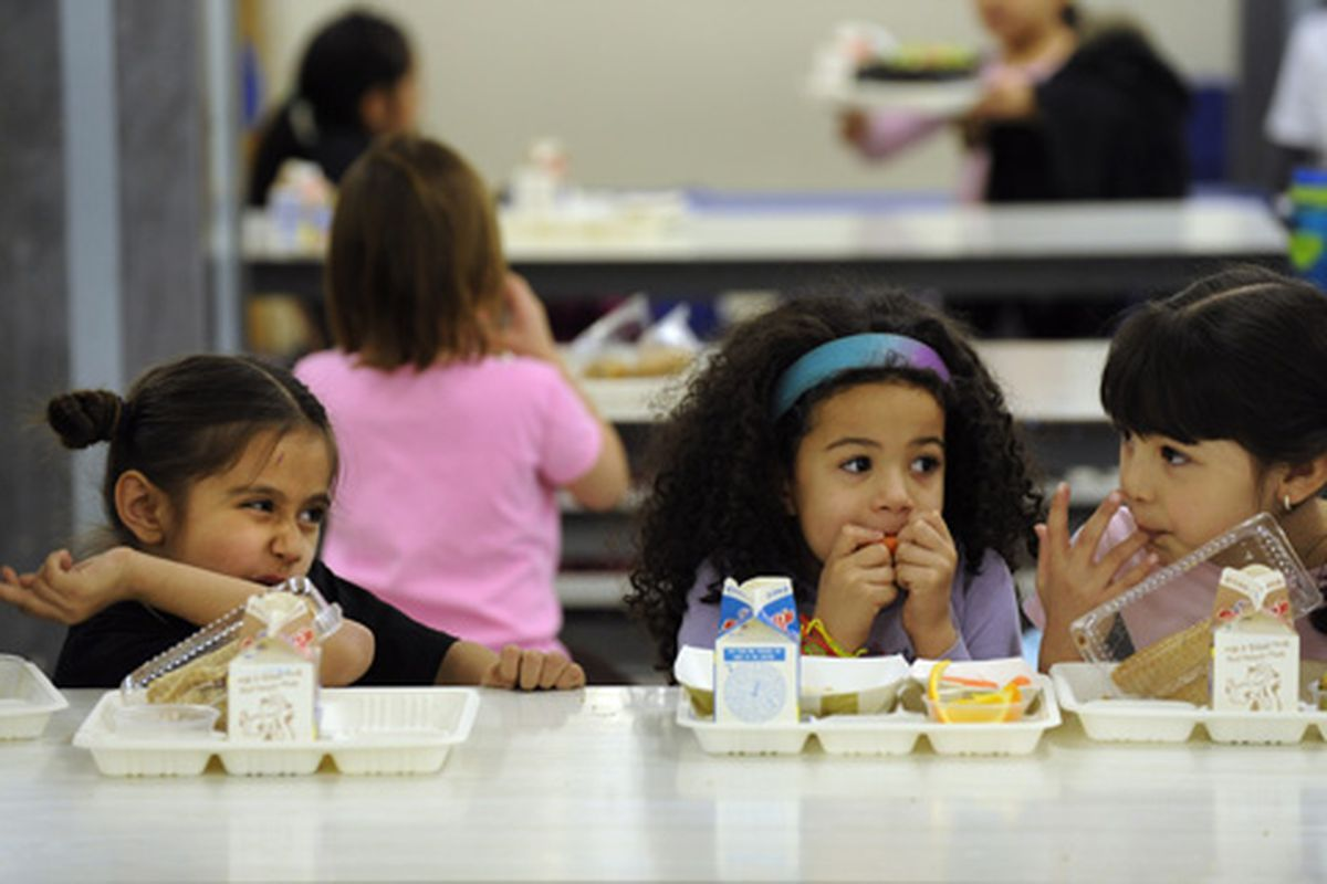 Students eat lunch in the cafeteria at Dora Moore K-8 School in Denver.