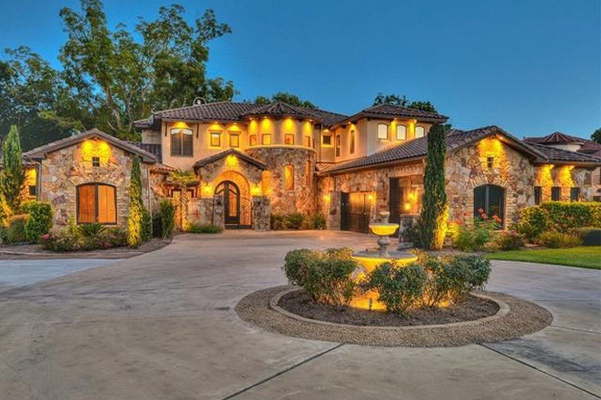 Large, Tuscan-style McMansion from front, many sections, circular driveway, at dusk, lighted up inside