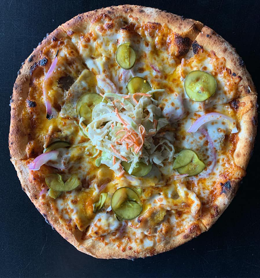 BBQ Pork pizza with cheddar and mozzarella cheeses, pork belly, and red onion