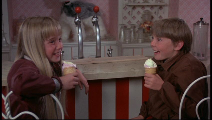 two alien kids eat ice cream at a parlor bar