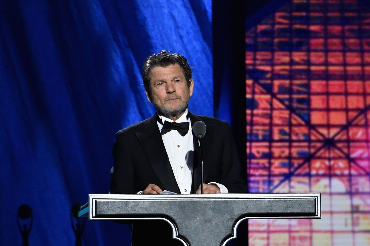 Rolling Stone founder Jann Wenner wears a tuxedo and stands behind a podium onstage at the Rock and Roll Hall of Fame.