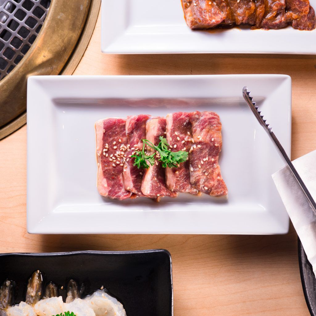 A plate of raw meat garnished with parsley and ready to be grilled at Gyu-Kaku