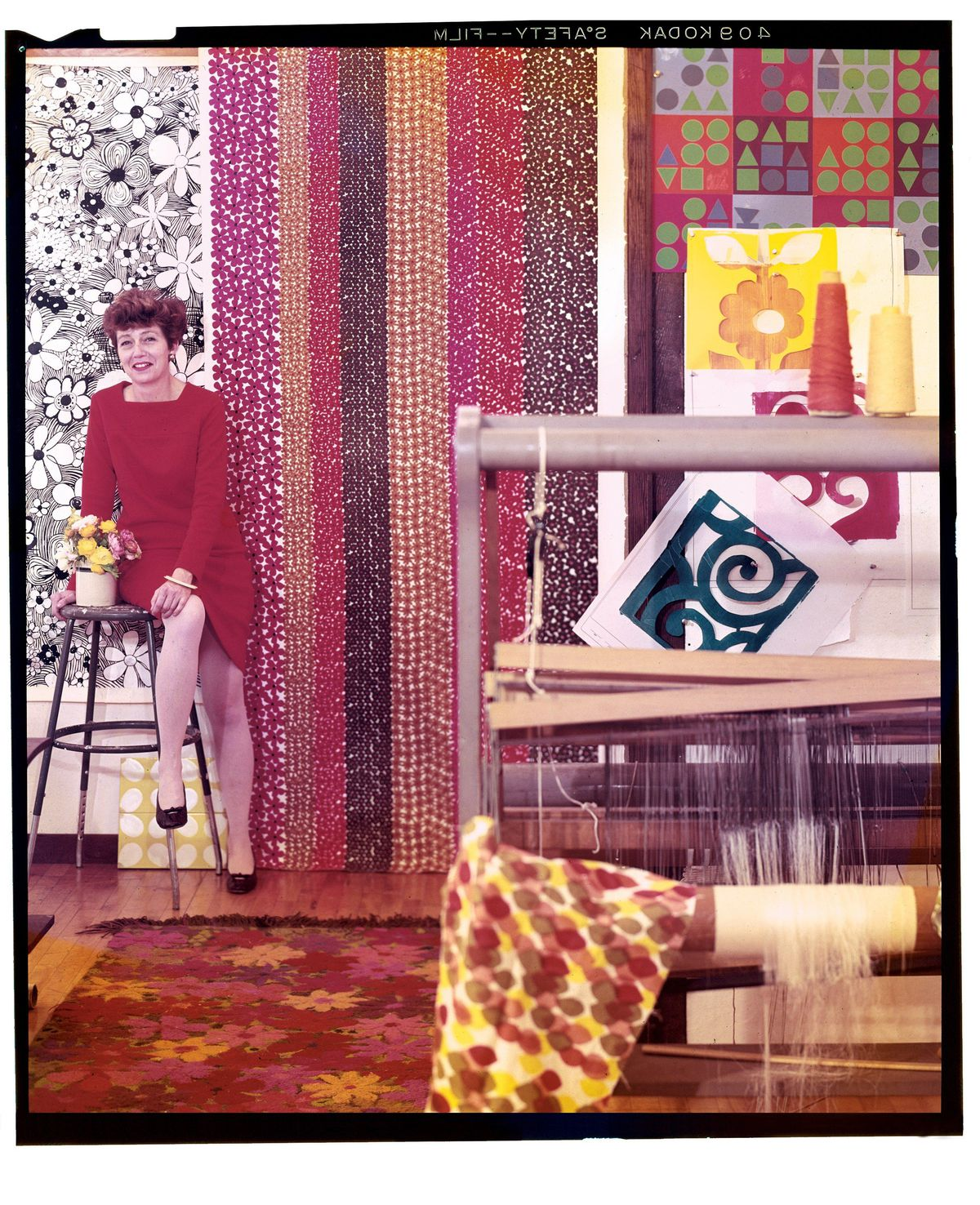 A woman in a red dress sits on a stool in a room heaped with fabrics, rugs and textiles, all in brightly colored, bold patterns.