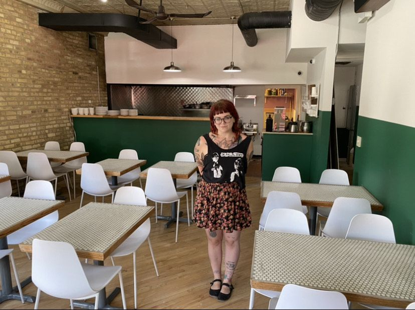 A person with red hair and glasses poses inside a restaurant.