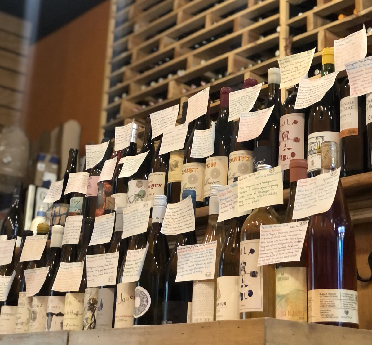 Wine bottles stacked on descending ledges with index card descriptions on the front of the bottles