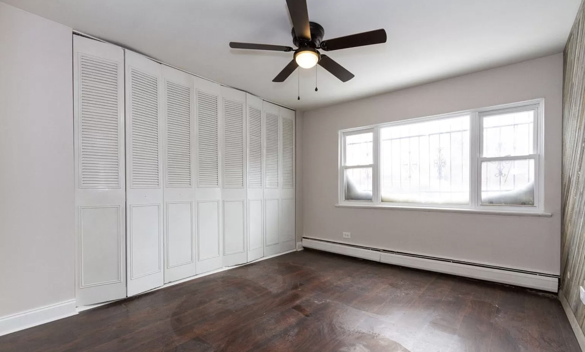 A bedroom with hardwood floors, a large window, a closet with a sliding door, and a fan.