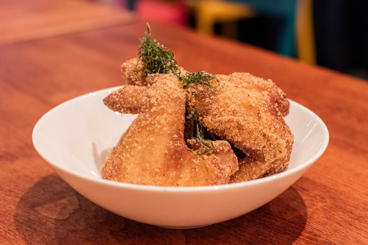 A white bowl with fried chicken wings.
