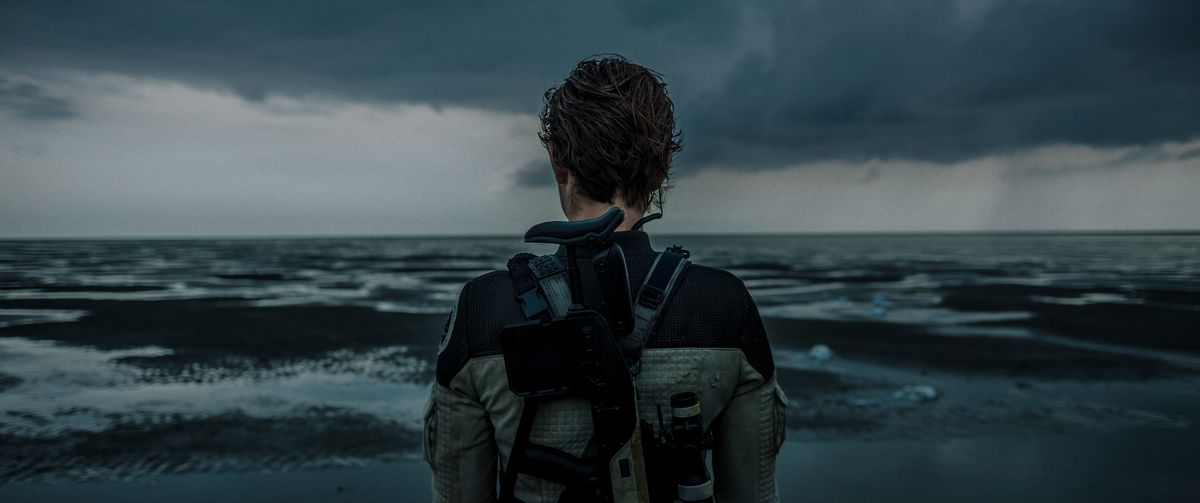 Nora Arnezeder looks out over the desaturated, depressingly grey ocean in The Colony