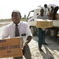 LDS missionaries Elder Sammuel Bassette, left, and Elder Lgune Raymond unload supplies for victims of the earthquake in Port-au-Prince, Haiti, Wednesday, Jan. 20, 2010.
