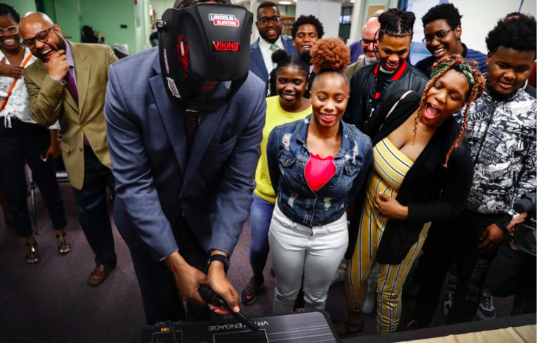 Martin Luther King College Prep students (right) and onlookers laugh as Shelby County Mayor Lee Harris (middle) attempts to use a virtual welding machine during a demonstration Nov. 19.