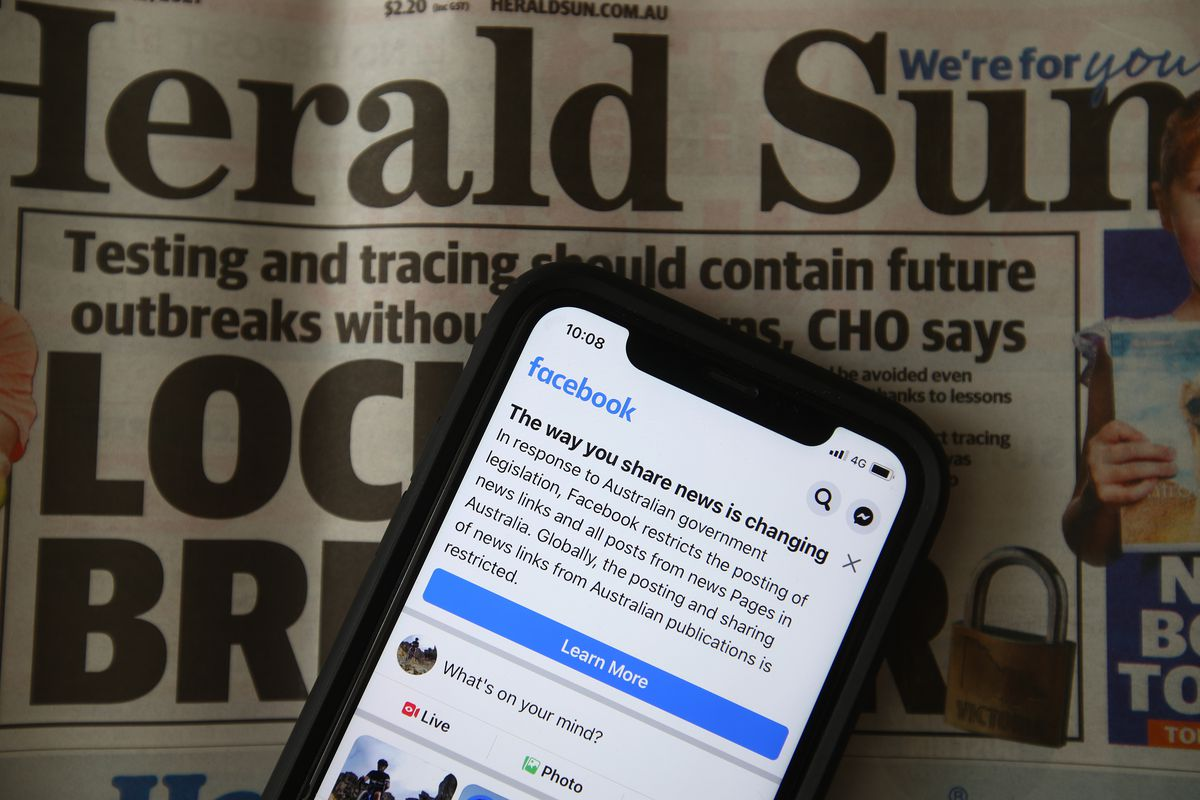 A photo of a phone with a Facebook post with an Australian newspaper in the background.