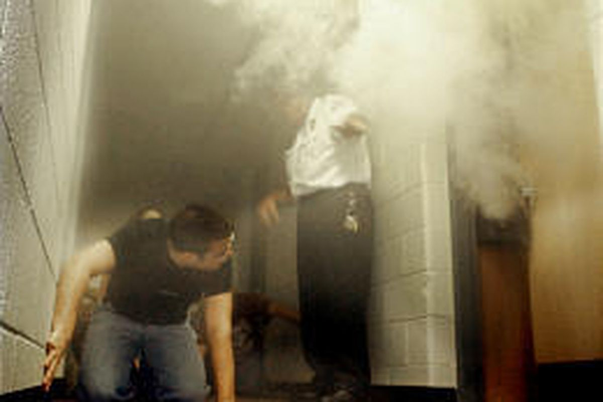 Resident advisers are directed through a smoke-filled dormitory floor during a fire safety drill at Rider University, a small independent university in New Jersey.