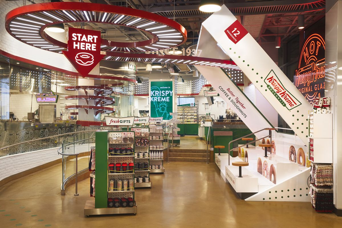 The interior of a store that sells retail merchandise and doughnuts with Krispy Kreme branding on the walls and products