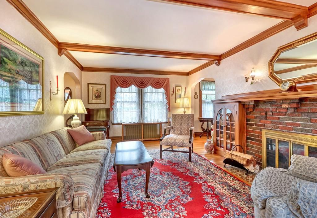 A spacious living room with a couch against the wall facing a large brick fireplace.