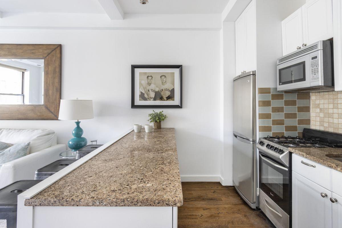 An open kitchen with an island with granite countertops, white cabinetry, and stainless steel appliances.