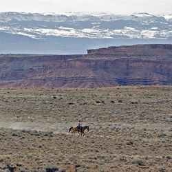Mike Vanderhoof crosses the plains while riding from the Sid's Mountain Wilderness Study Area back to camp in the San Rafael Swell  Friday, April 1, 2011, in the San Rafael Swell in Central Utah.